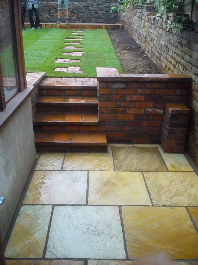Brick wall and steps with materials found in the garden and a Fossil Sandstone patio