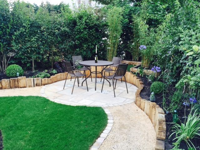 Oak sleepers boarder the garden retaining the flower beds. Indian Sandstone patio with Moroccan Tiles set in  to the pattern