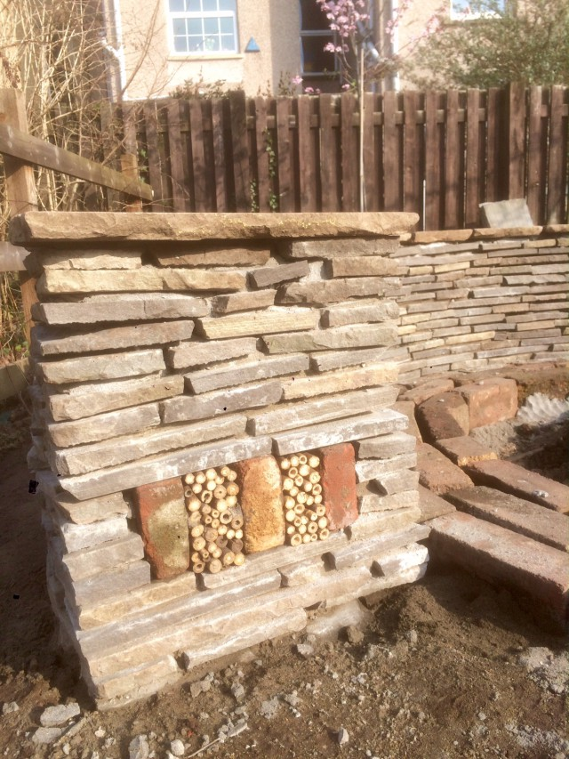 Sandstone semi circular bench with bug house